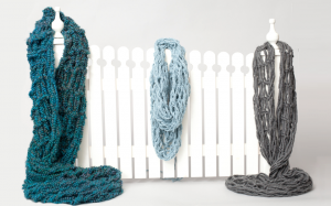 arm knitted scarves on picket fence